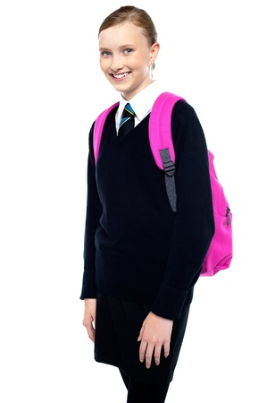 uniform skirt: Casual shot of a cheerful girl in school uniform carrying backpack. Stock Photo