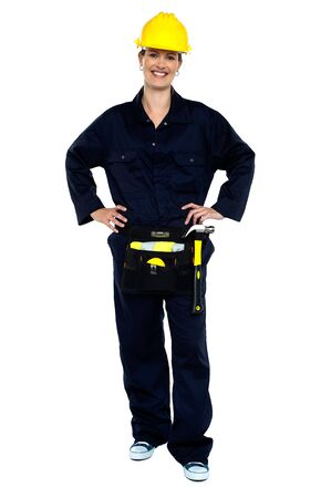 Active woman construction worker in overalls posing with hands on waist. photo