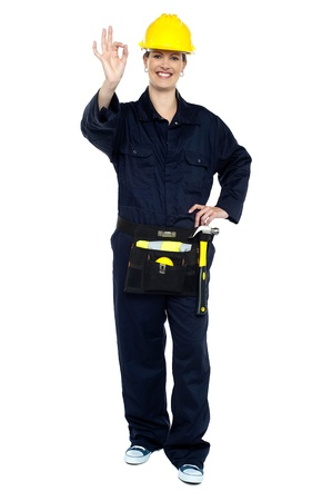 Female worker in jumpsuit showing perfect gesture. Work is good. photo