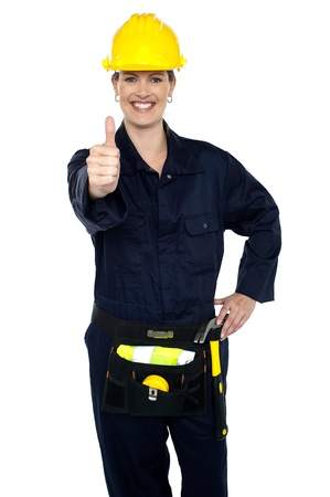 good work: Keep up the good work. Confident lady worker showing thumbs up to you.