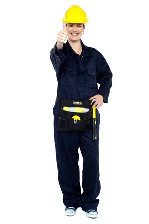 Energetic construction worker in yellow helmet showing thumbs up sign.