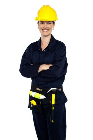 Confident cheerful female architect with tool kit around her waist. photo