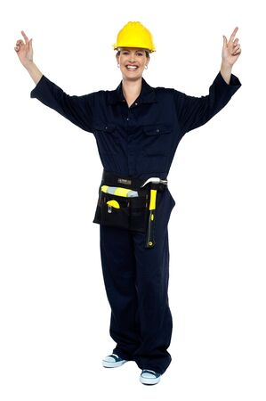 Smiling lady worker in jumpsuit raising her hands in jubilation. All on white background. photo
