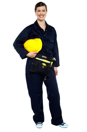 Full length studio shot of a relaxed construction worker with yellow helmet. photo