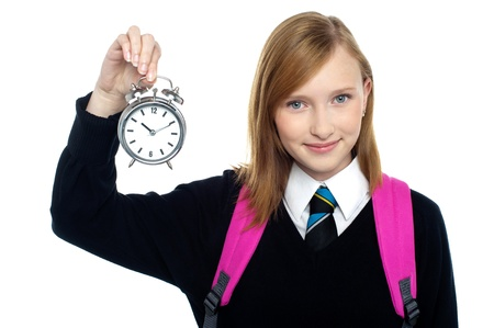 Pretty charming schoolgirl holding time piece isolated against white.