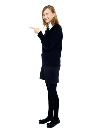 school uniform girl: Student standing sideways and pointing forward. Copy space concept