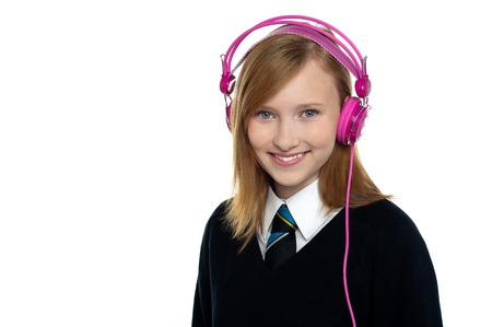 Cute teenager listening to music through headphones. All on white background. photo