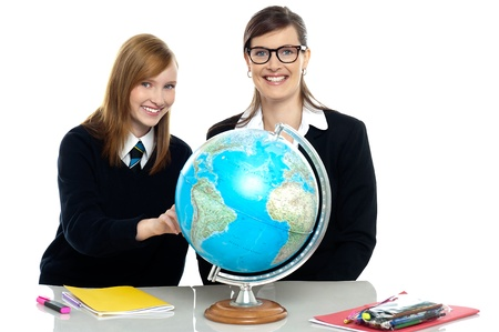 High school teacher and student viewing globe in geography classroom. Stock Photo - 16686844