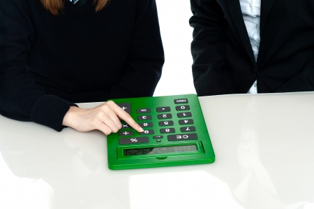Cropped image of teacher and a student working out on a large green calculator. photo