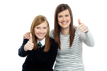 posing  agree: Charming daughter with her mother showing thumbs up sign to the camera.