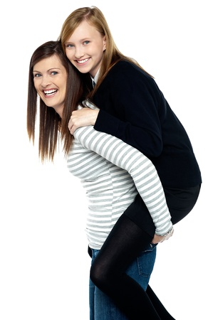 Fun loving duo of mother and daughter. Piggy ride fun. photo