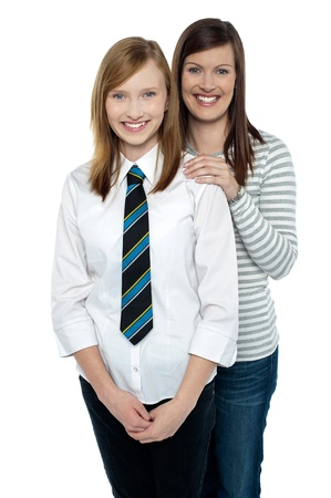 Blonde mother and daughter posing together isolated against white background. photo