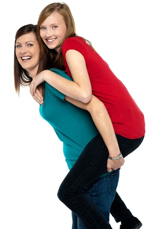 Happy mother giving piggy back ride to her daughter isolated on white background. photo