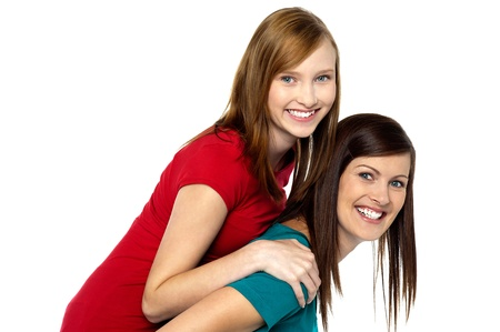 piggyback ride: Mother piggybacks her teenage girl. All against white background. Stock Photo