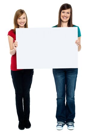 Pair of good looking women holding whiteboard. Full length portrait. photo