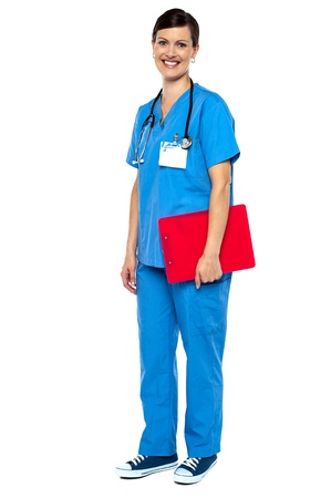 Nurse wearing blue uniform and holding red clipboard. Full length studio shot. Stock Photo - 16684988