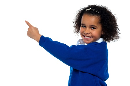 curly hair child: Adorable African kid pointing at copy space area while facing the camera.