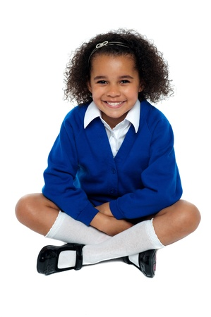 Charming African school girl flashing a smile. Studio shot photo