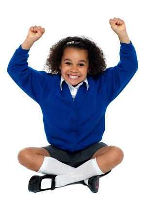 Primary school girl grinding her teeth in excitement. Sitting on floor with crossed legs. Stock Photo - 16771520
