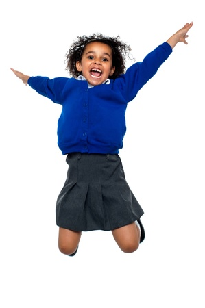 school children uniform: Excited jubilant school kid jumping high up in the air after hearing her annual result. Stock Photo