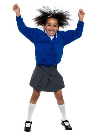 Pretty African school girl dances in full swing. Isolated over white background. Stock Photo - 16771498