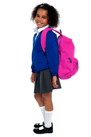 Curly haired elementary school girl carrying pink backpack on shoulders. Stock Photo - 16771509