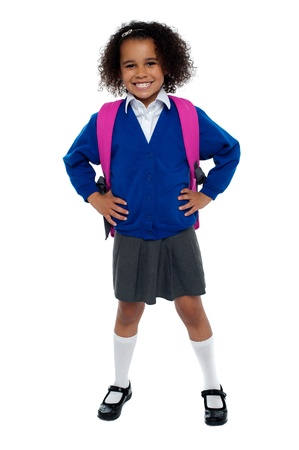 school band: Primary school girl posing confidently with hands on her waist, carrying pink school bag.
