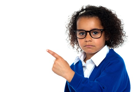 Primary class student. Studio shot of a melancholic girl pointing sideways. Stock Photo - 16771525