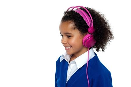 Charming young kid listening to music using pink headphones. Stock Photo - 16771518