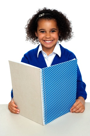 Smiling school girl learning weekly assignment. Looking confident before the examinations. Stock Photo - 16771549