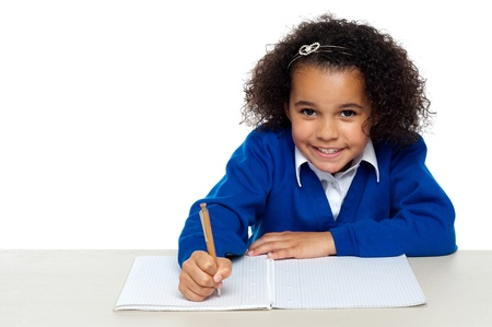 school girl uniform: Studio shot of a cute primary kid writing her assignment. Stock Photo