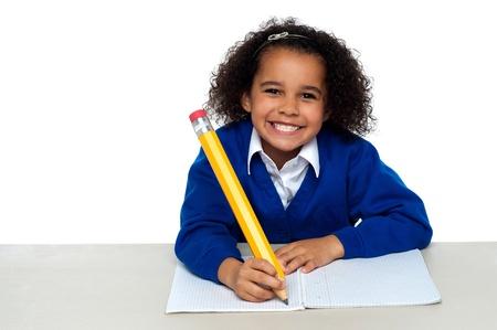 ni�os escribiendo: Muchacha bonita escribiendo en su cuaderno y el parpadeo sonrisa por rechinar los dientes. Foto de archivo