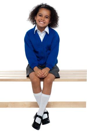 Hübsches Schulmädchen gemütlich auf einer Bank mit ihren Beinen sitzen gekreuzt.