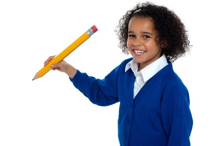 school girl uniform: Lovely elementary girl facing the camera with a pencil in hand. Isolated over white background. Stock Photo