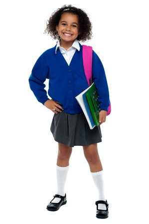 school bag: Girl in smart uniform holding notebook and calculator in hand and carrying pink backpack over shoulders.