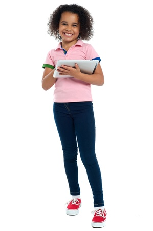 indoor shot: Primary child with a tablet pc smiling cheerfully. Indoor shot over white.
