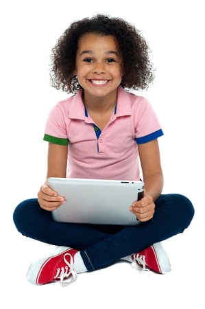 floor standing: Cool girl kid sitting on the floor with wide grin on face holding tablet pc. Stock Photo