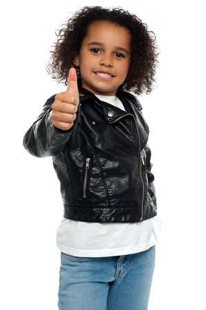 yup: Stylish child savoring sweet success by gesturing thumbs up.