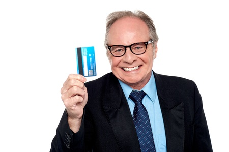 Business concept, old man wearing eyeglasses holding up a cash card. photo
