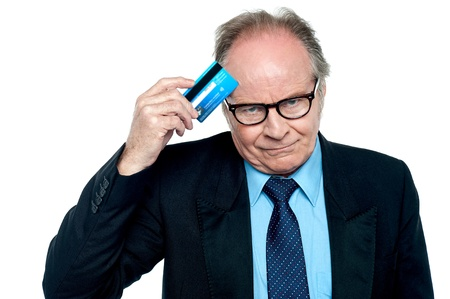 Pensive looking businessman scratching his forehead with credit card over white background. photo