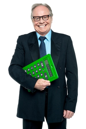 Successful senior male manager with a big green calculator in his hand. photo