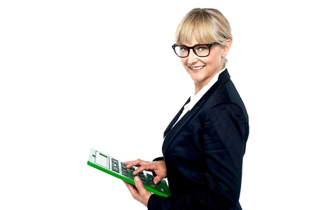 Bespectacled entrepreneur using a calculator while smiling at the camera. photo