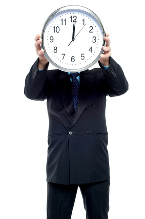 Smartly dressed businessman holding wall clock in front of his face. photo