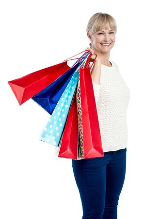 Stylish woman with colorful shopping bags slung over her shoulder. Stock Photo - 17081666