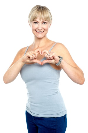 Will you be my valentine? Romantic middle aged woman gesturing heart shape. photo