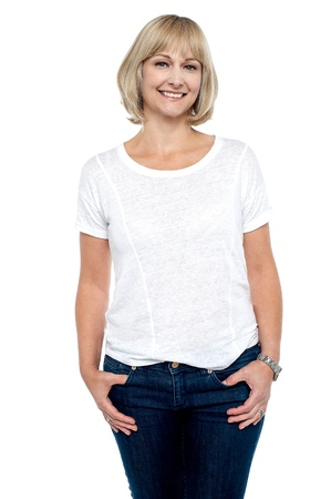 Middle aged woman in trendy clothing smiling at you, studio shot. photo