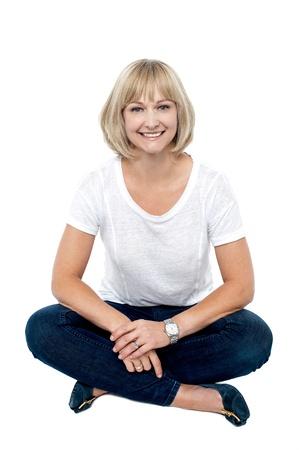 mujer sentada: Sonriente mujer de mediana edad sentada en el suelo, tiro del estudio sobre blanco. Foto de archivo