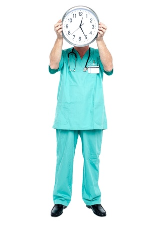 time critical: Surgeon holding a clock. Time is critical for the patients survival.