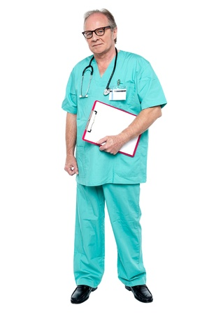 Portrait of grim faced doctor holding a clipboard standing against white background. Stock Photo - 17081692