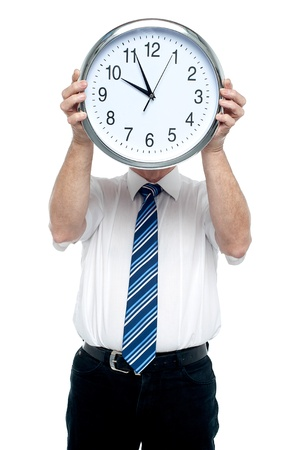 Boss holding a clock in front of his face. Get ready for the meeting in five minutes! photo